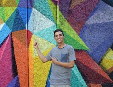 Javier delante del mural de Okudart