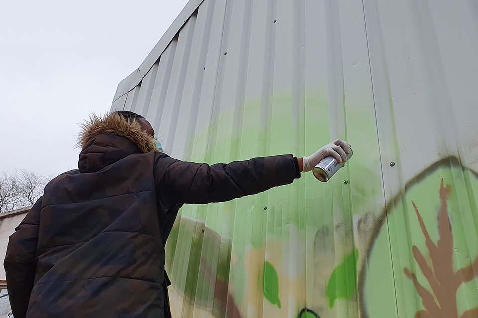 estudiante pintando con botes de spray en las salidas escolares