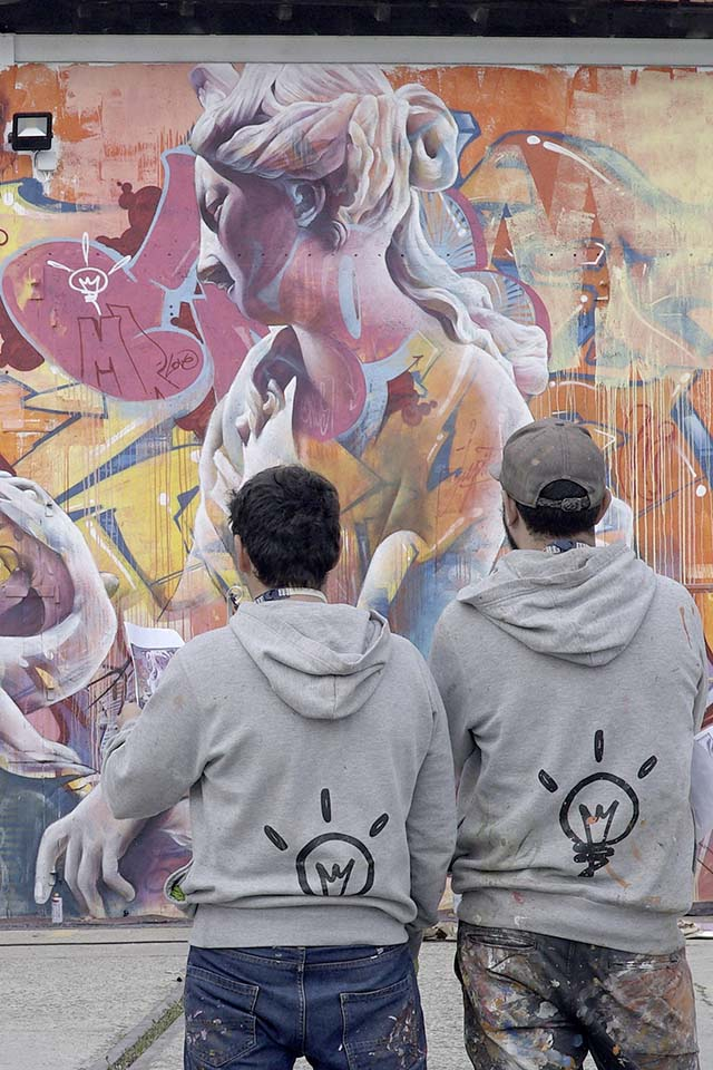 fotografía de dos artistas en frente de su obra